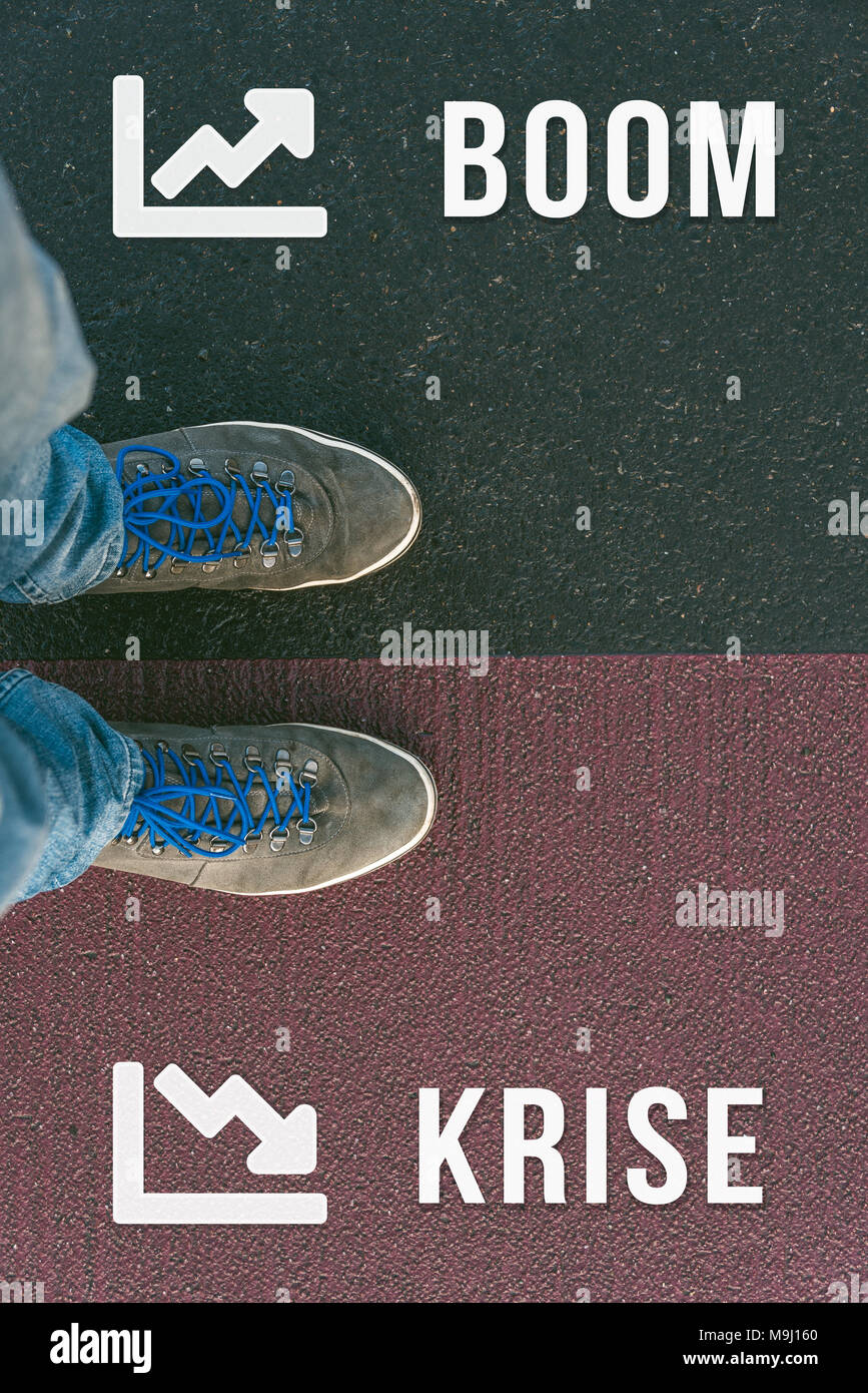 Reaching a crossroads having to choose between boom and krise meaning crisis in german symbolized by two feet standing on two different colors with ar - Stock Image
