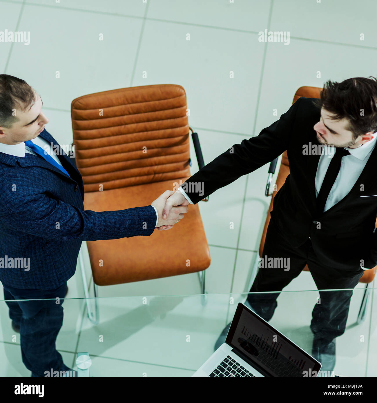 handshake business partners near the desktop, in the spacious office - Stock Image