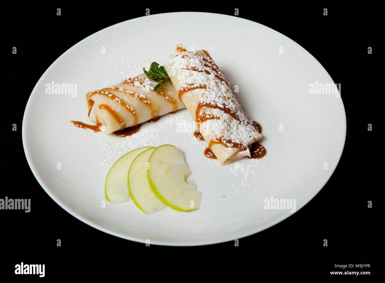 Pancakes with apples on a black background. Restaurant menu. Stock Photo