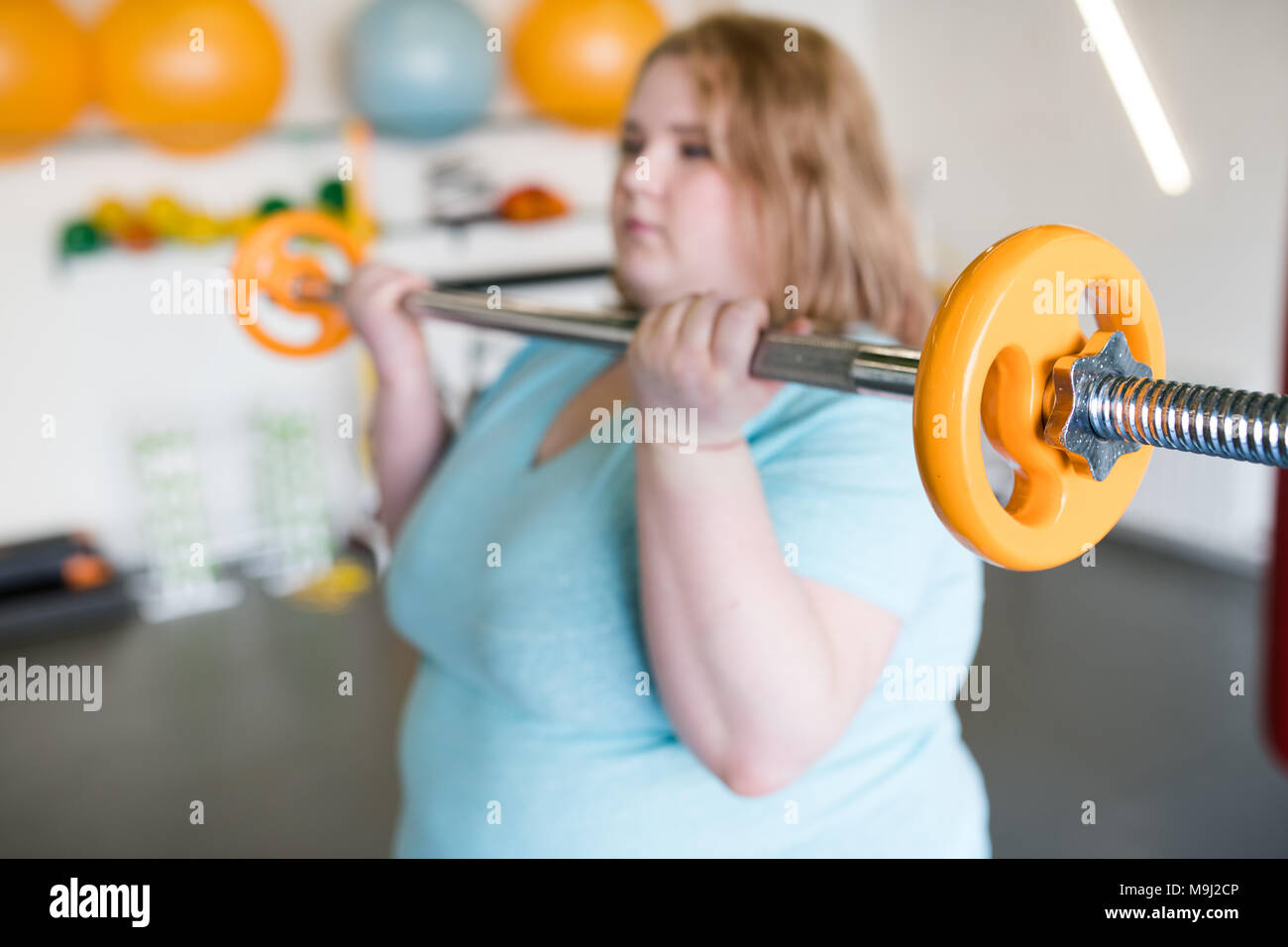 Obese Woman Working Out with Barbell - Stock Image