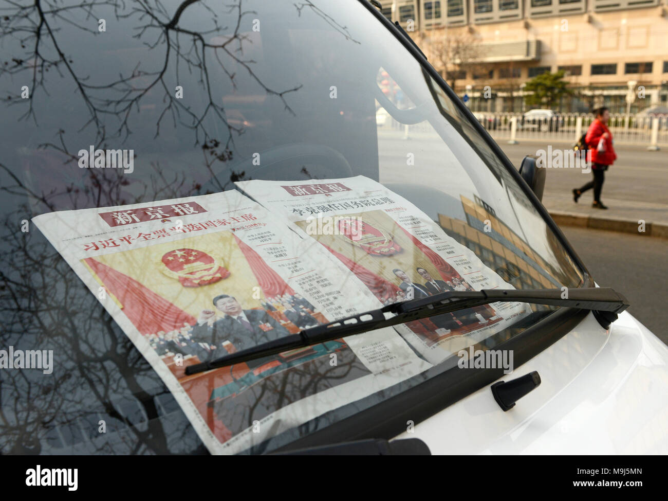 President Xi Jinping features on the front page of newspapers in a van window on a street in central Beijing, China - Stock Image