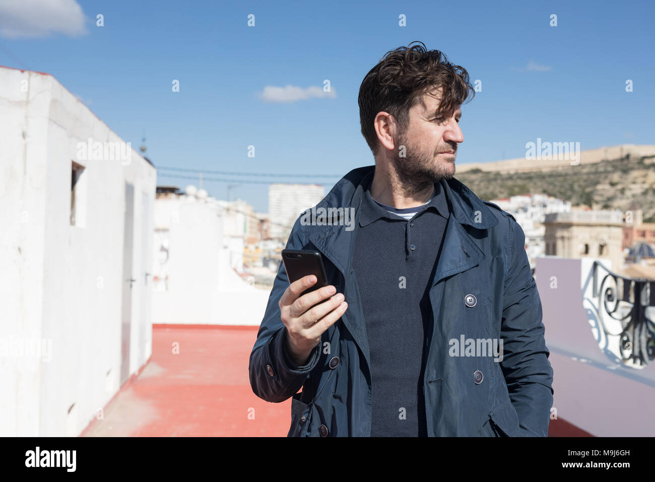 portrait of 45 year old man with blue jacket and mobile in his hand - Stock Image