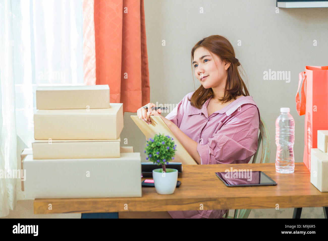 Young happy attractive female asian online seller working at home in her bedroom, thinking about her successful online business Stock Photo