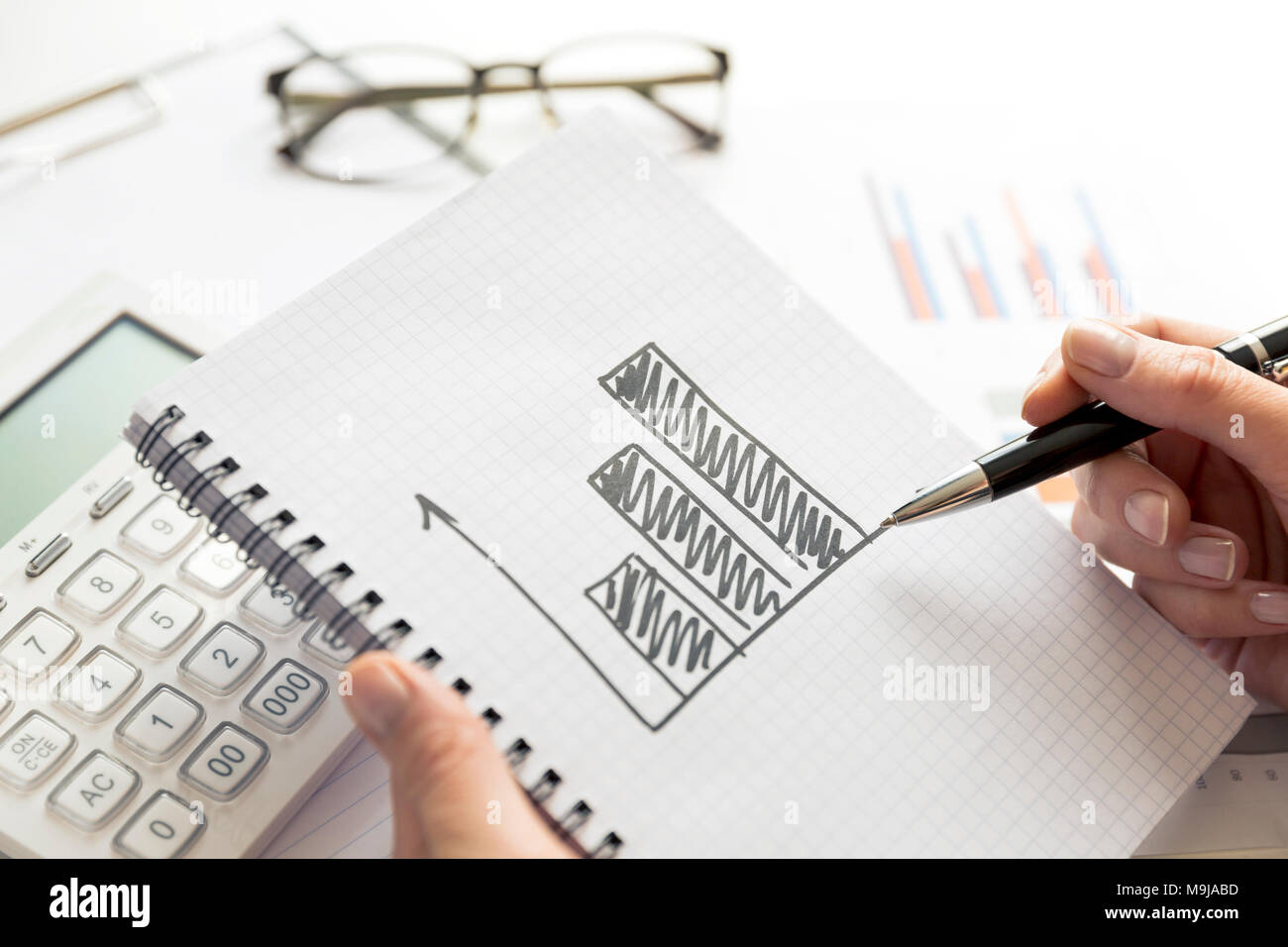 Businesswoman working on project about business growth. Drawing of a growing graph in notebook - Stock Image