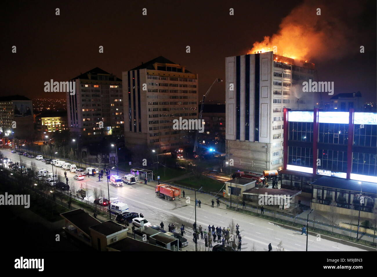 Grozny, Russia. 26th Mar, 2018. GROZNY, RUSSIA - MARCH 26, 2018: Top floors of a twelve-storey apartment building have caught fire in central Grozny, the capital of Chechnya. Yelena Afonina/TASS Credit: ITAR-TASS News Agency/Alamy Live News - Stock Image