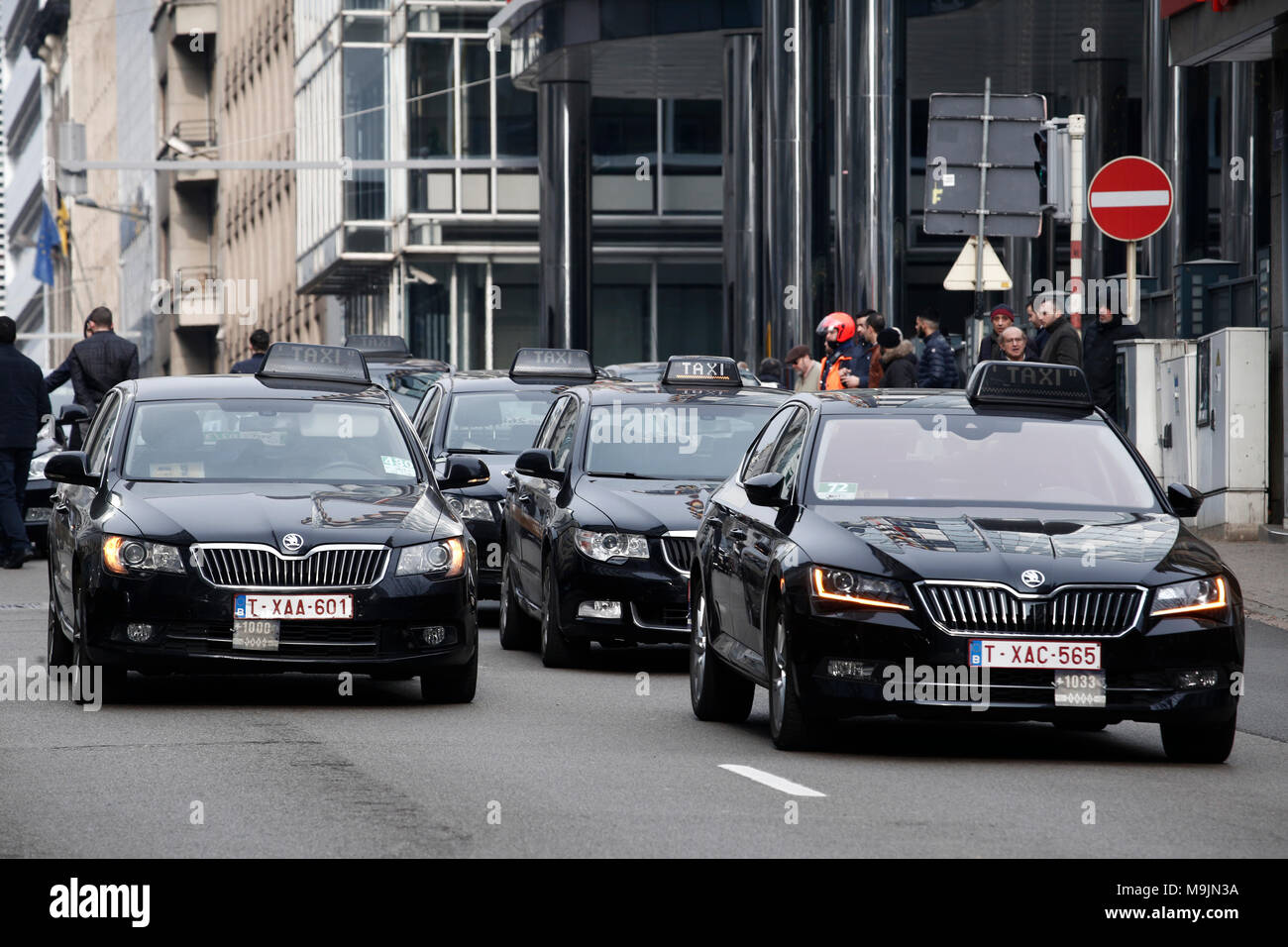 Taxi drivers use their vehicles to block roads during a