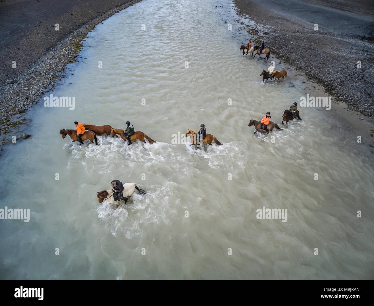 Horses crossing Farid glacial river near Hagafellsjokull Glacier, Iceland - Stock Image