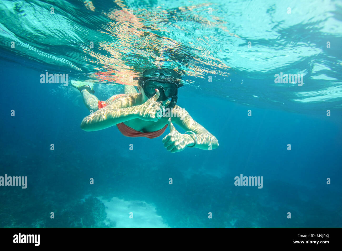 Young woman in orange bikini and scuba mask, holding two thumbs up, Similan Islands (Phang Nga), Thailand, one of the best snorkeling locations in And - Stock Image