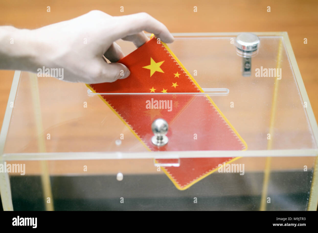 Man inserting Flag of China into ballot box, voting and elections in China. - Stock Image