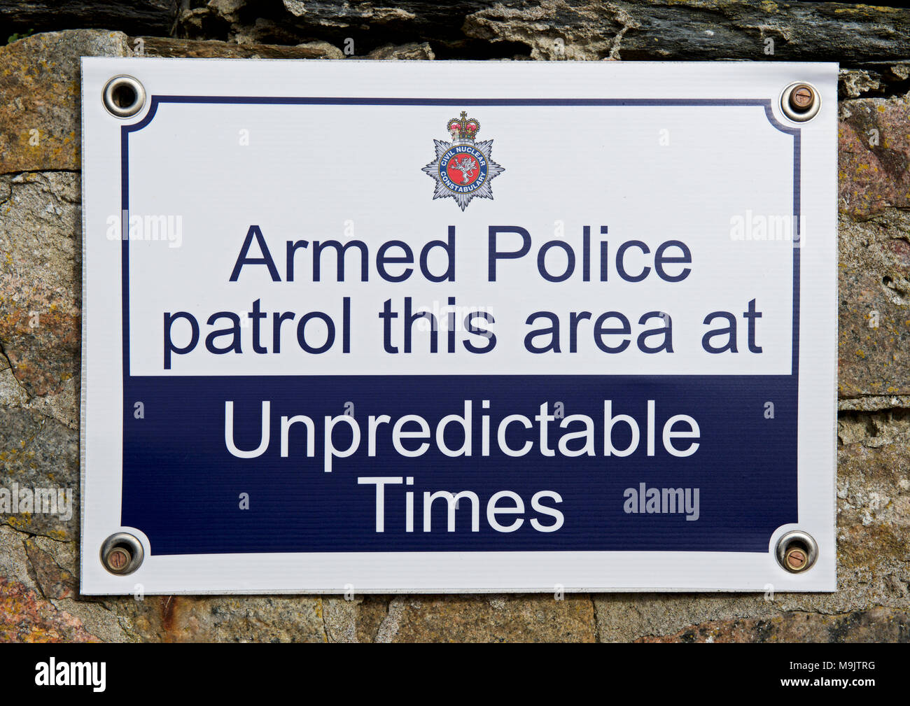 Sign: Armed police patrol this area at unpredictable times, England UK - Stock Image
