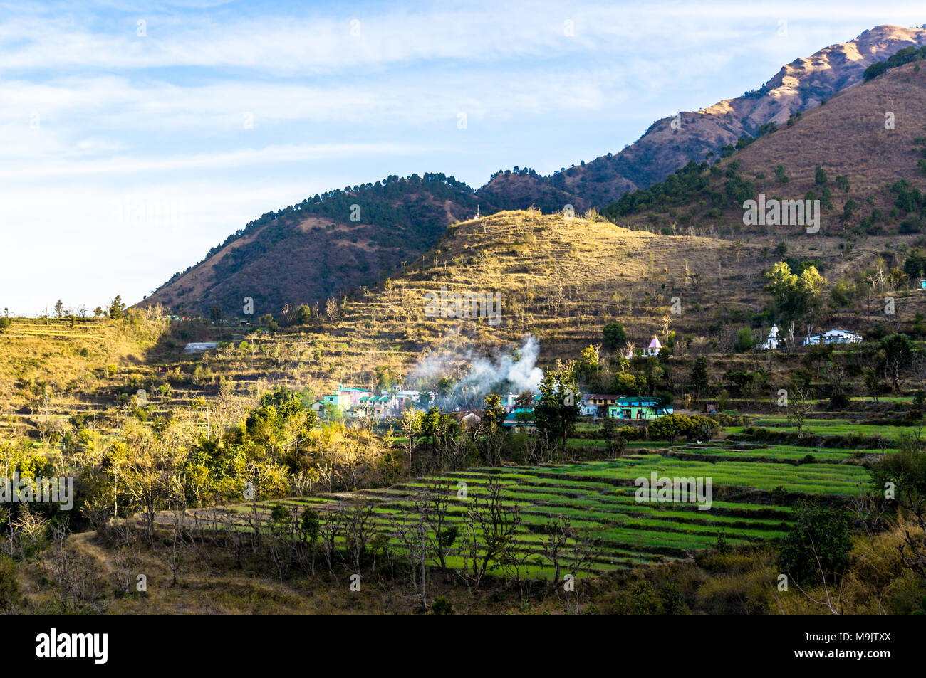 Landscape shot of Dehradun with a village on a hillside. The smoke coming from the village, the grassy stepped fields and beautiful surroundings make this a perfect tourism shot - Stock Image