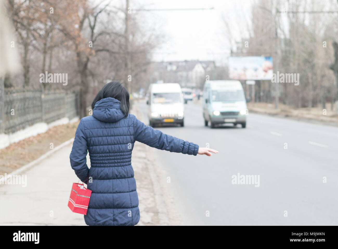 CHISINAU, MOLDOVA - 3 JANUARY, 2017: A lady trying to stop a minibus with the usual sign in Chisinau- by lifting an arm. - Stock Image