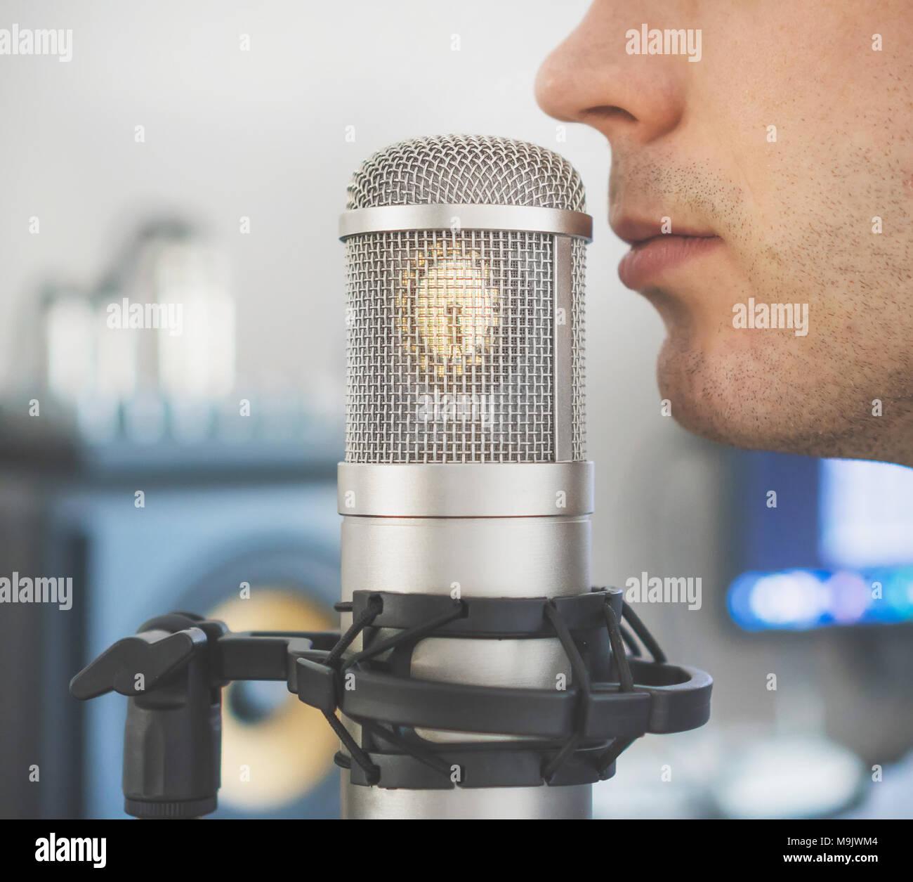 Man near microphone in the record studio. - Stock Image