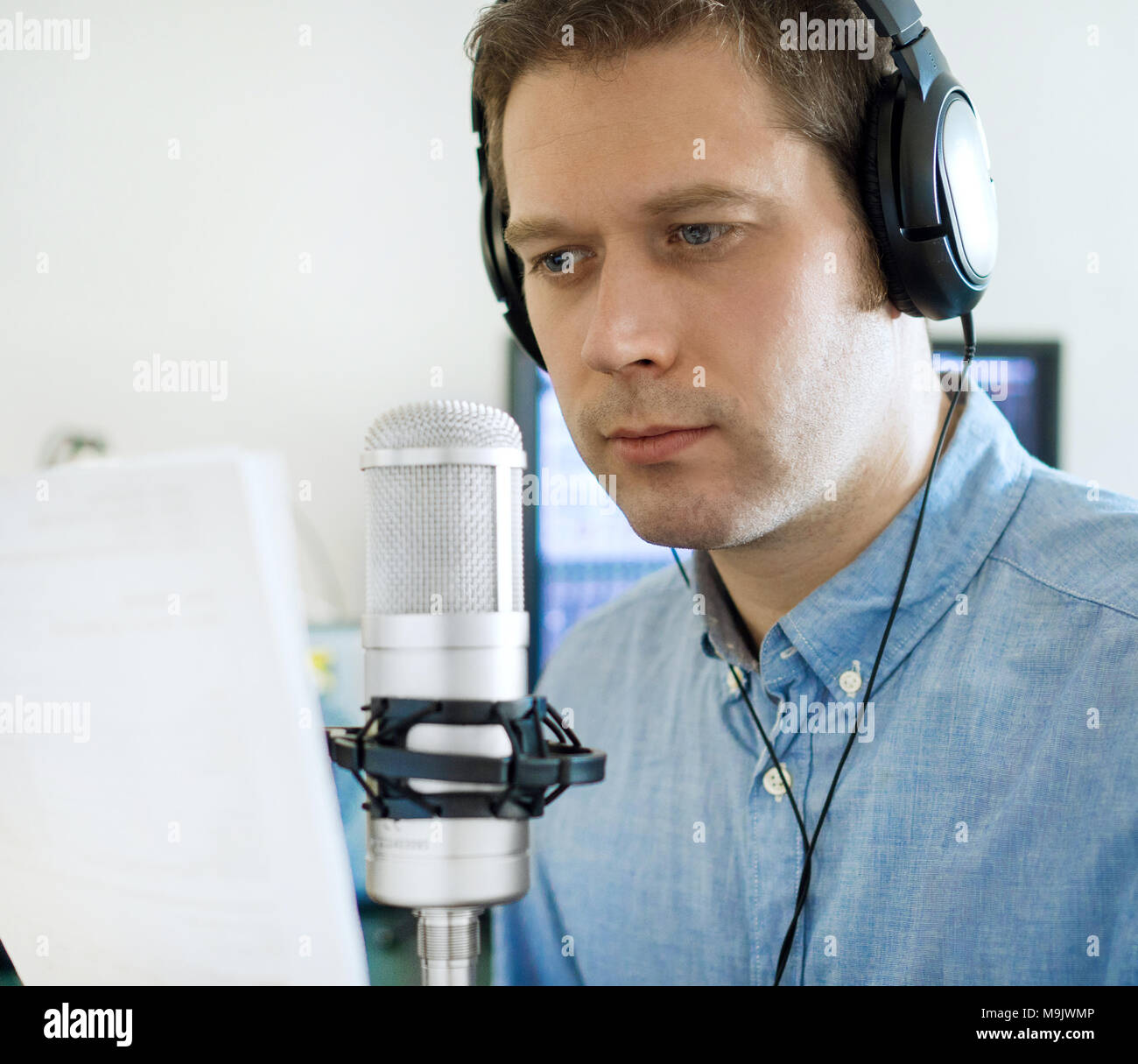 Handsome man recording an advertisement on the radio station. - Stock Image