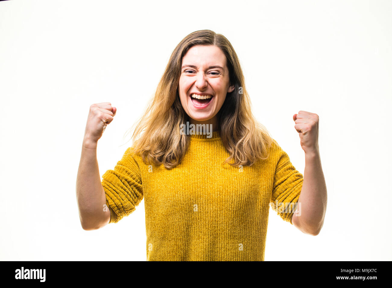 Celebrating success - A happy smiling positive enthusiastic  young Caucasian woman girl , pumping her fists in exuberance, full of passion and committment  - UK - Stock Image