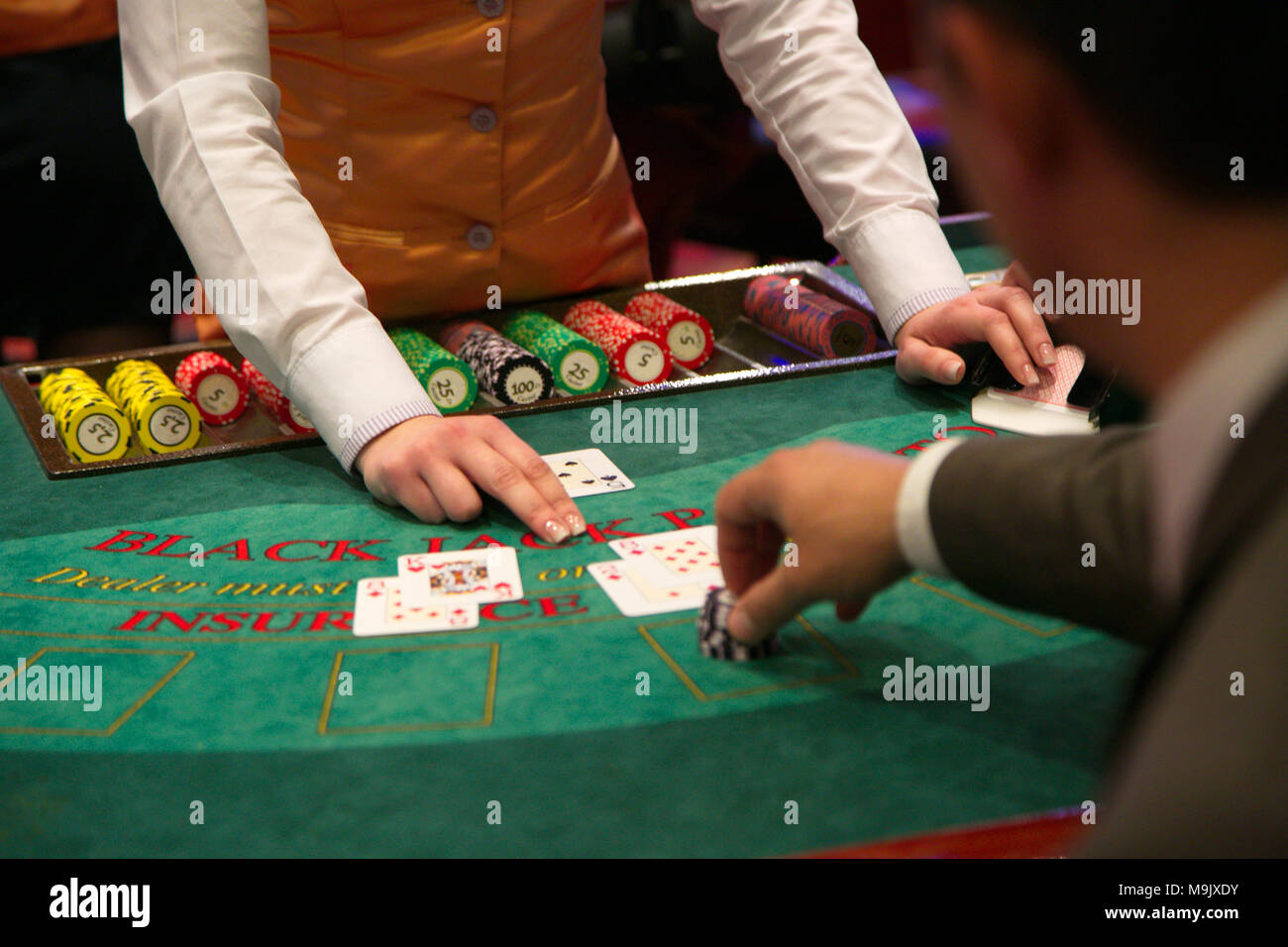 Dealer puts down a card on blackjack table - Stock Image