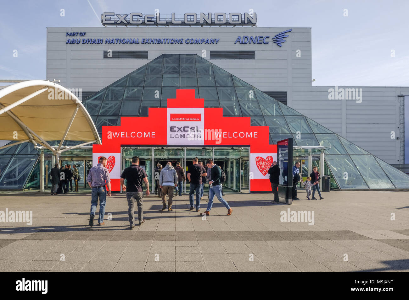 London, UK - February 16, 2018:  towards the entrance of Excel Exhibition Centre at Royal Docks, London, with people walking towards the doors. - Stock Image