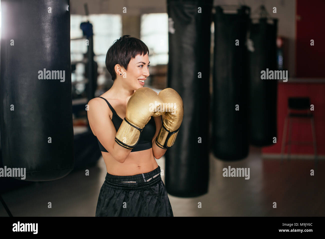 side view image of smiling woman in black sporty suit showing boxing blow at gym.combat sport. boxing skills - Stock Image