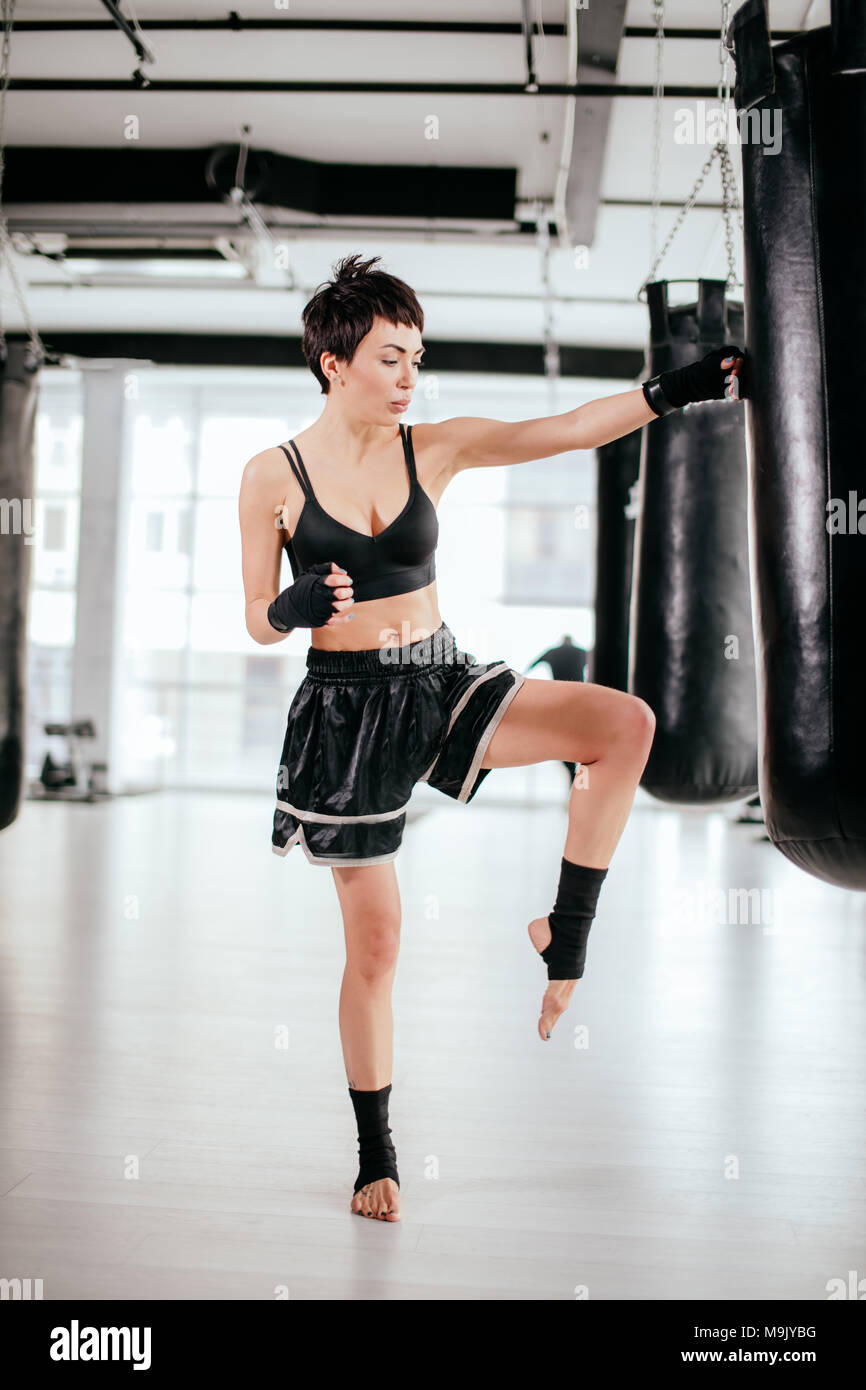 attractive athlete in black sporty shorts and top standing with raised bent knee on one leg next to boxing bag. - Stock Image