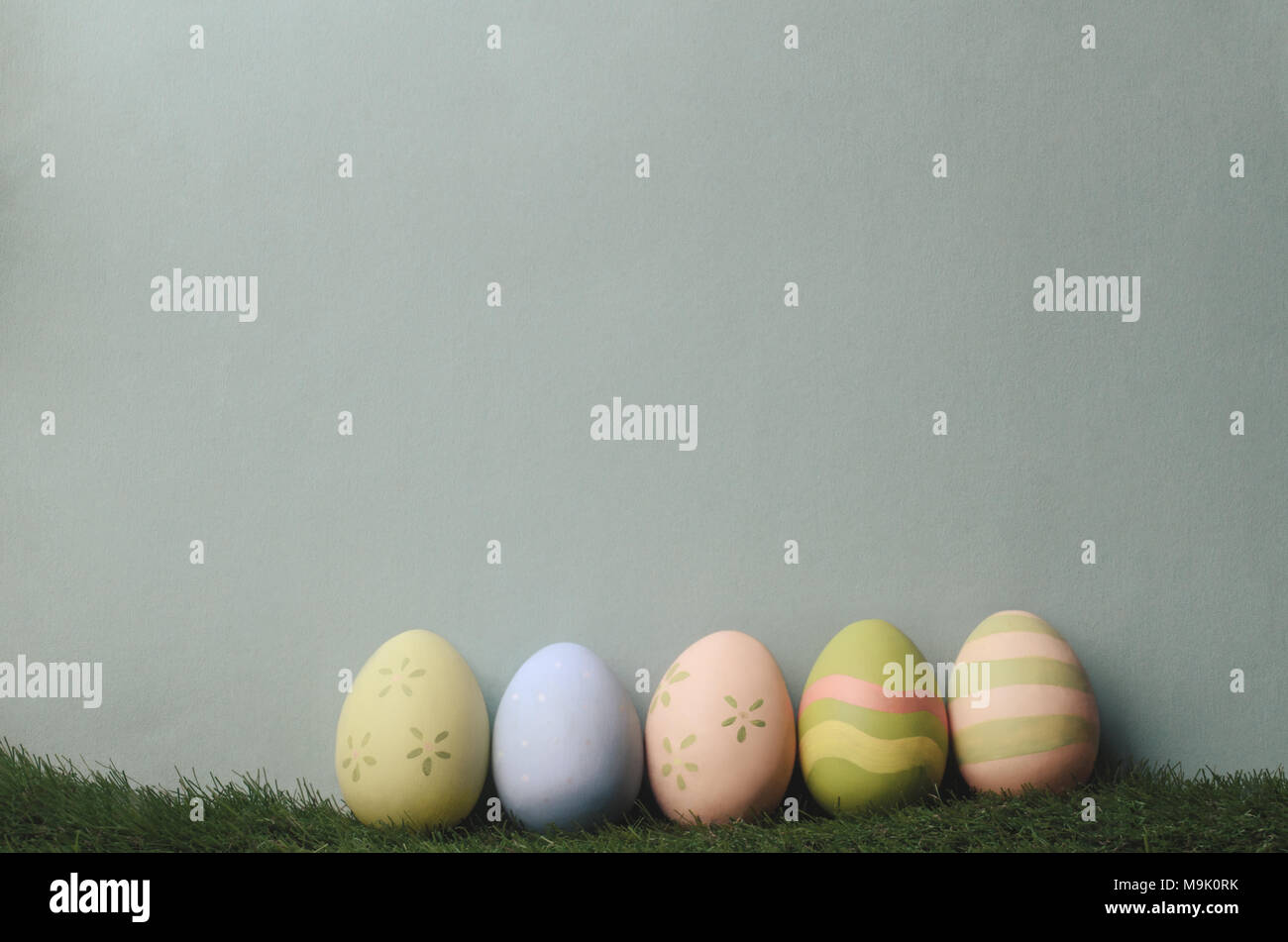 A row of decorated eggs in different colours on artificial grass against blue grey background for Easter. Filtered to give muted, retro style. - Stock Image