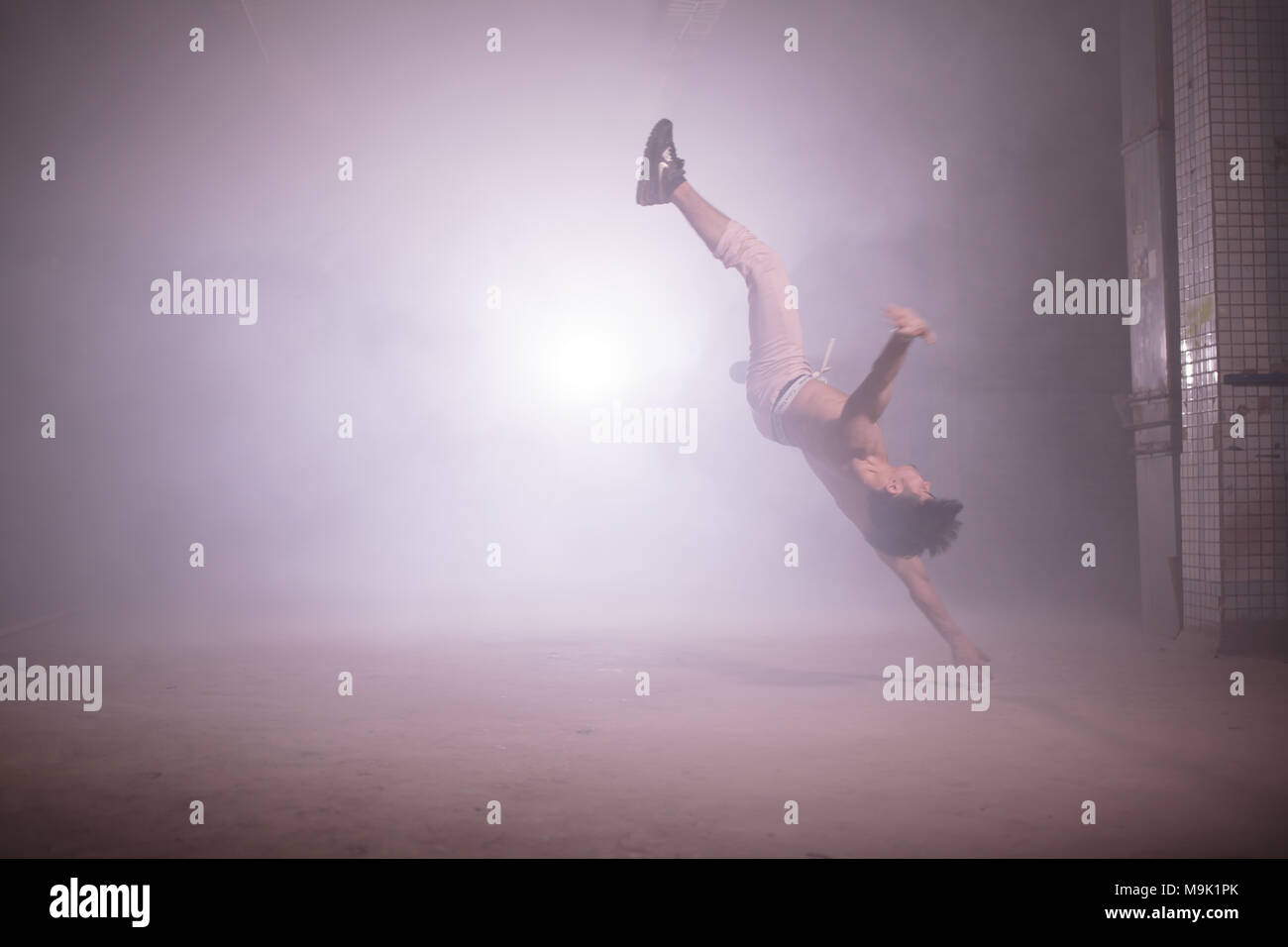 young stuntman performing the trick in the air. making complex movements. air spinning. airflare, airtwist - Stock Image