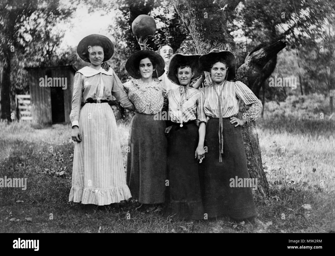 A young man with a basketball photobombs four women posing for a picture, ca. 1910. - Stock Image