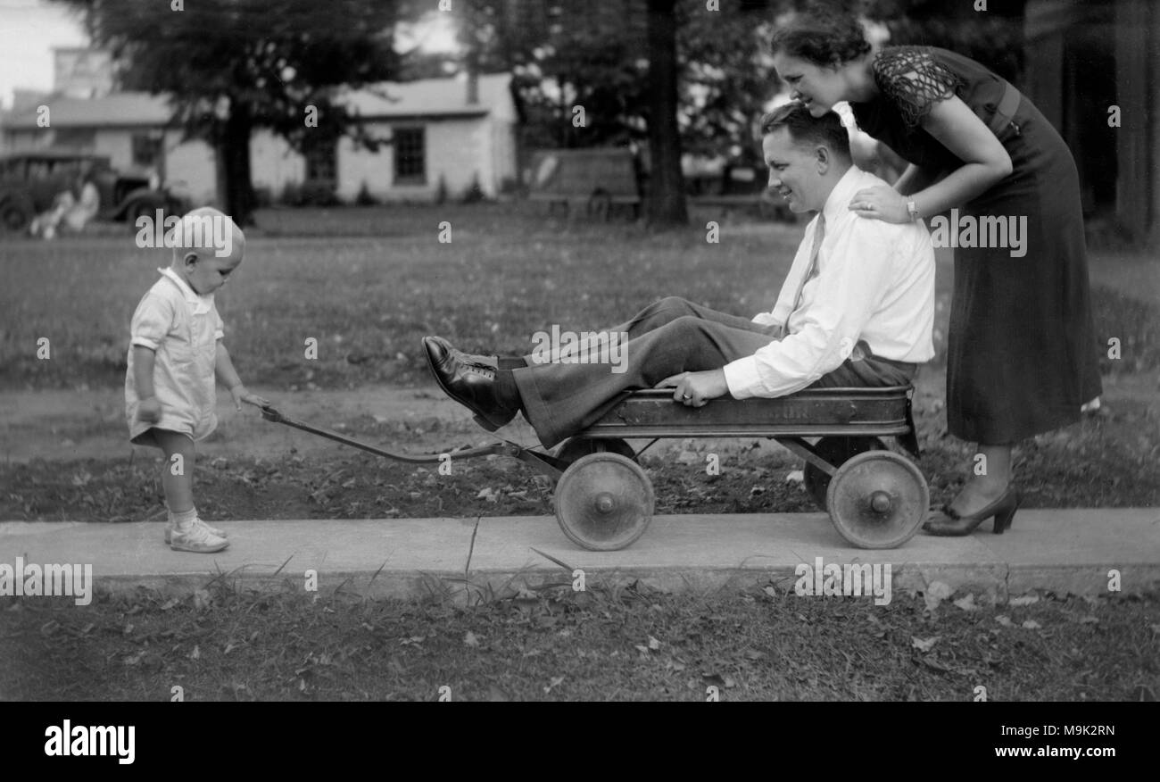 Wagon-bound dad is stuck between a pushy wife and pulling toddler son, ca. 1920. - Stock Image