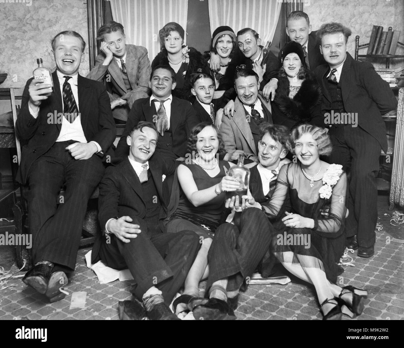 """Young people drink bootleg whiskey labled """"Old Log Cabin"""" during Prohibition in Chicago in 1927.  """"Old Log Cabin"""" was Canadian Club Whiskey imported by gangster Al Capone and Bugs Moran then rebottled and distributed in the Chicago area. - Stock Image"""
