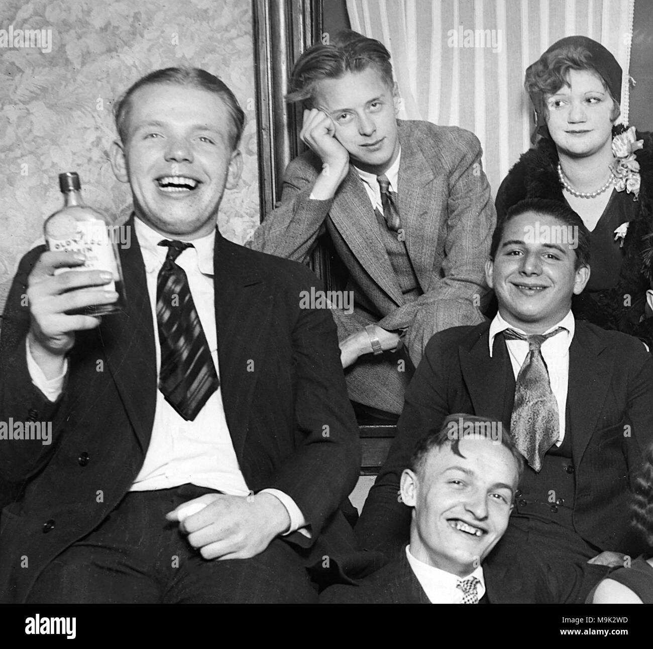 """Young people drink bootleg whiskey labeled """"Old Log Cabin"""" during Prohibition in Chicago in 1927.  """"Old Log Cabin"""" was Canadian Club Whiskey imported by gangster Al Capone and Bugs Moran then rebottled and distributed in the Chicago area. - Stock Image"""
