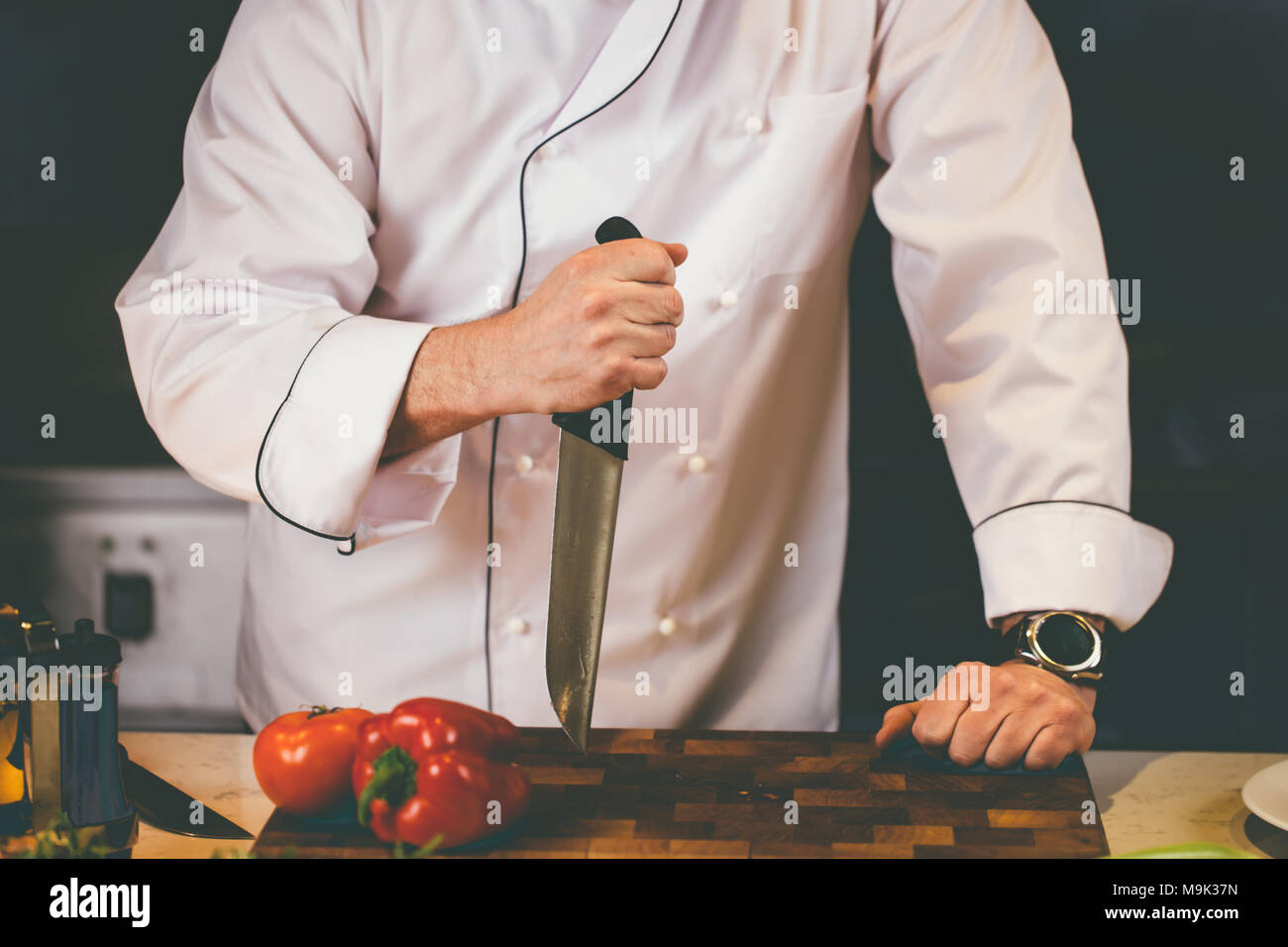 close up photo of a large knife being stucked on the cutting board. angree shef. forceful cook.lead cook - Stock Image