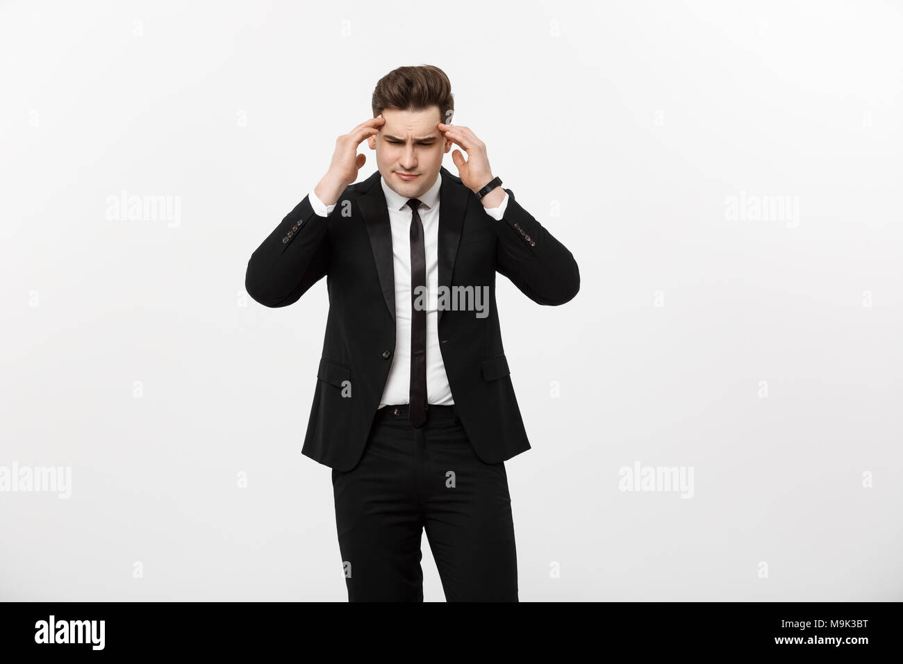 Business Concept: Young handsome businessman with pain in his temples. Photo of man suffering from stress or a headache grimacing in pain. - Stock Image