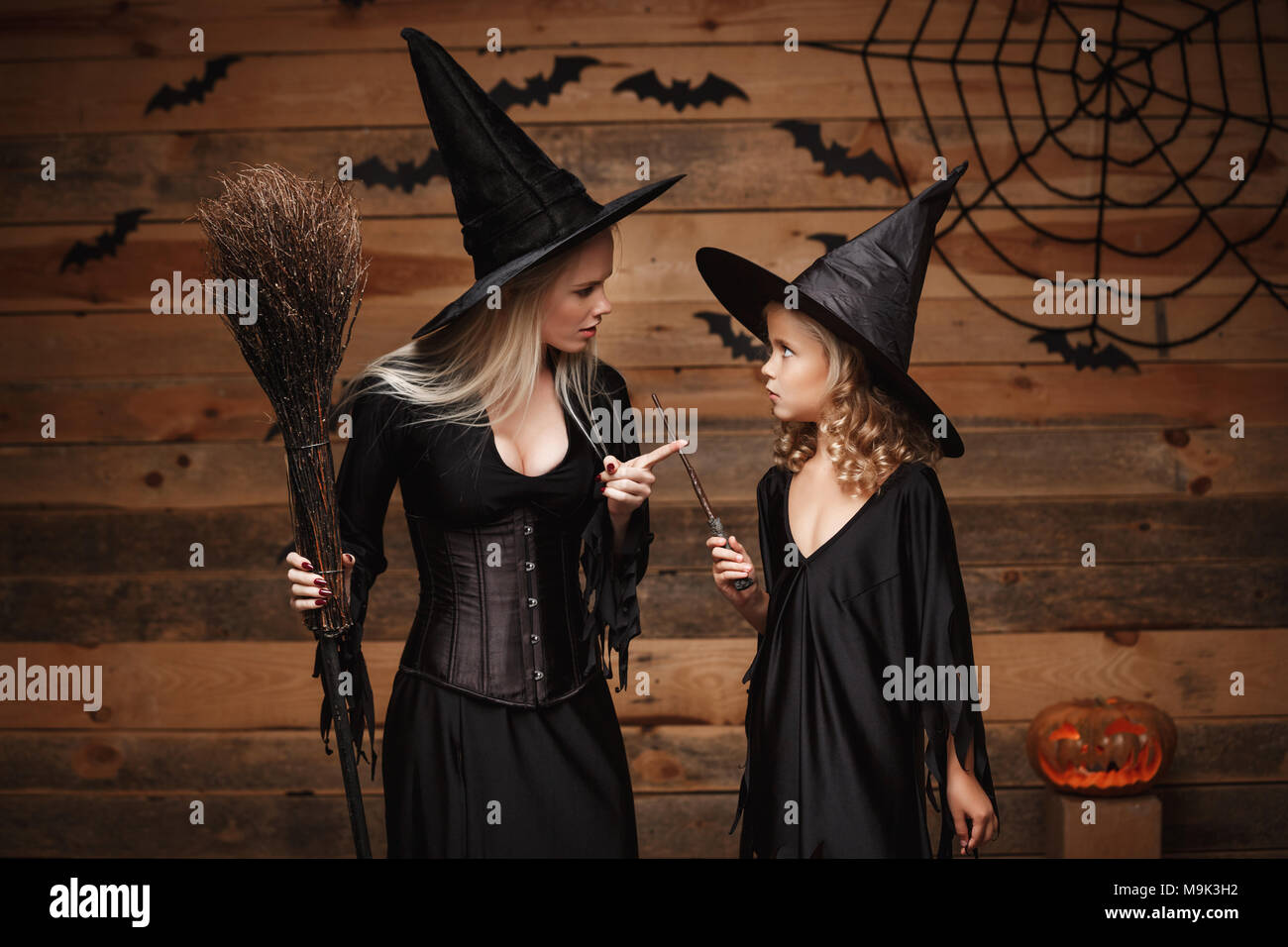 Halloween Concept - stressful witch mother teaching her daughter in witch costumes celebrating Halloween with curved pumpkins over bats and spider web on Wooden studio background. - Stock Image