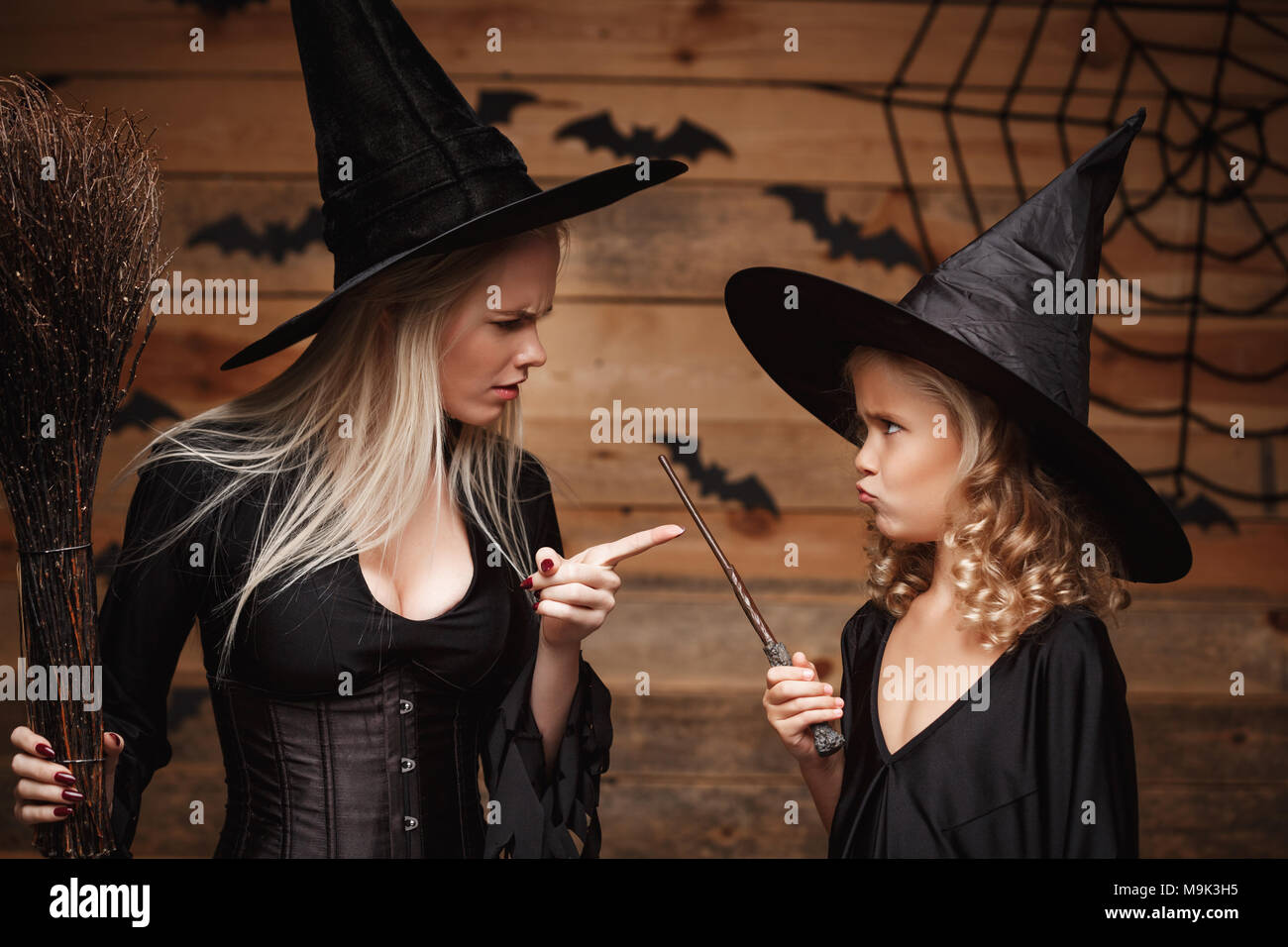Halloween Concept - stressful witch mother teaching her daughter in witch costumes celebrating Halloween over bats and spider web on Wooden studio background. - Stock Image