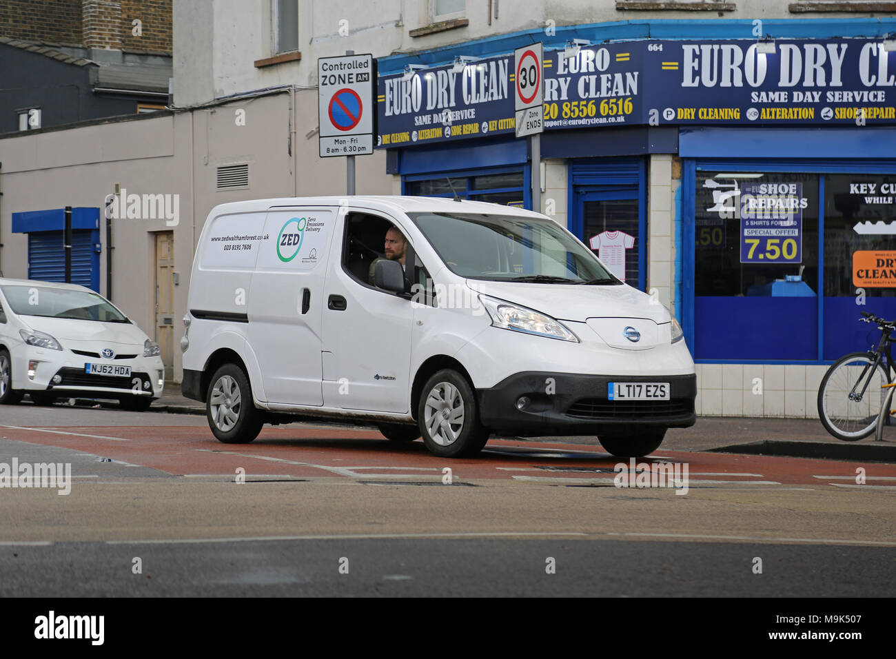 A white Nissan e-NV200 electric van makes deliveries in North London, UK. Branded: Zero Emissions Deliveries' - Stock Image