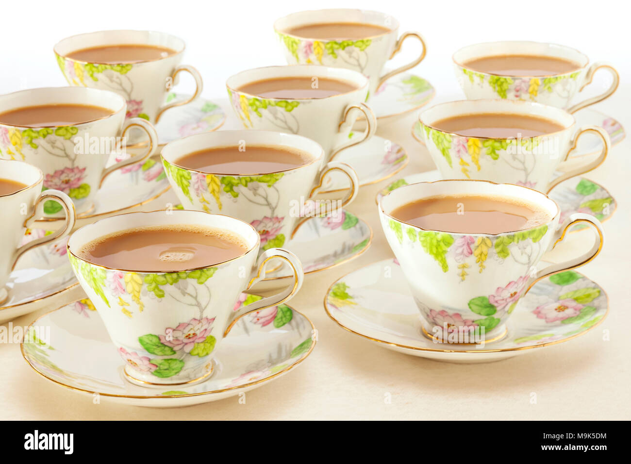 Tea Concept - cups of freshly poured tea in beautiful antique crockery. This image can be fully customised with the name of your cafe or tea room. Ple - Stock Image