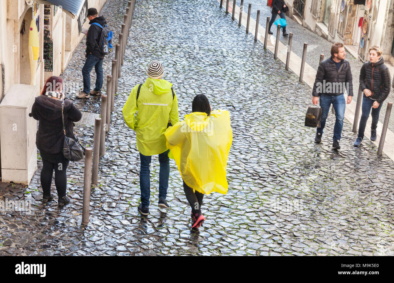 1 March 2018: Lisbon Portugal - Couple wearing yellow plastic rain capes in the old town of Lisbon on a wet day. - Stock Image