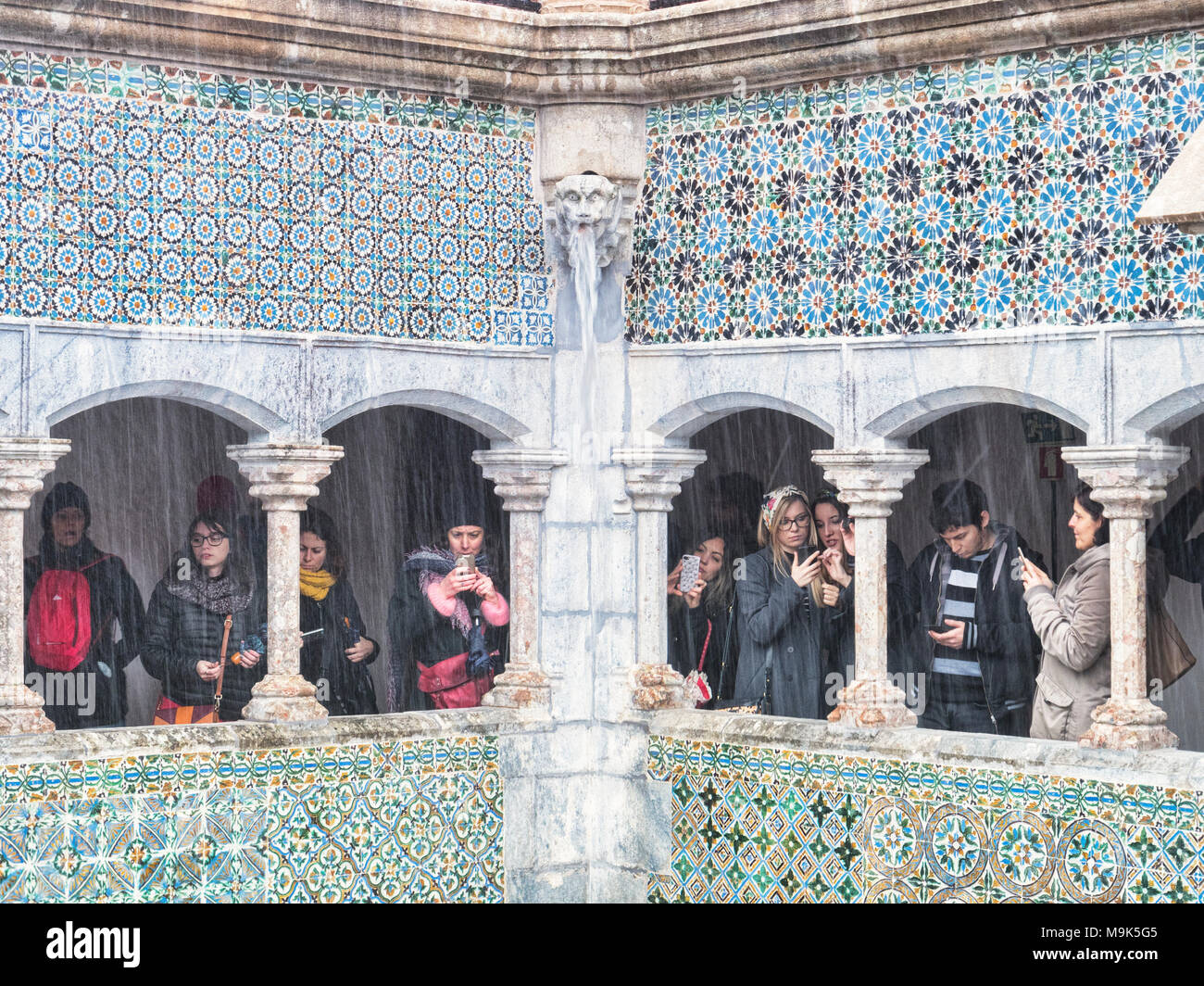 5 March 2018: Sintra, Portugal - Tourists with camera phones under a colonnade at Pena Palace, making the most of a very wet day. - Stock Image