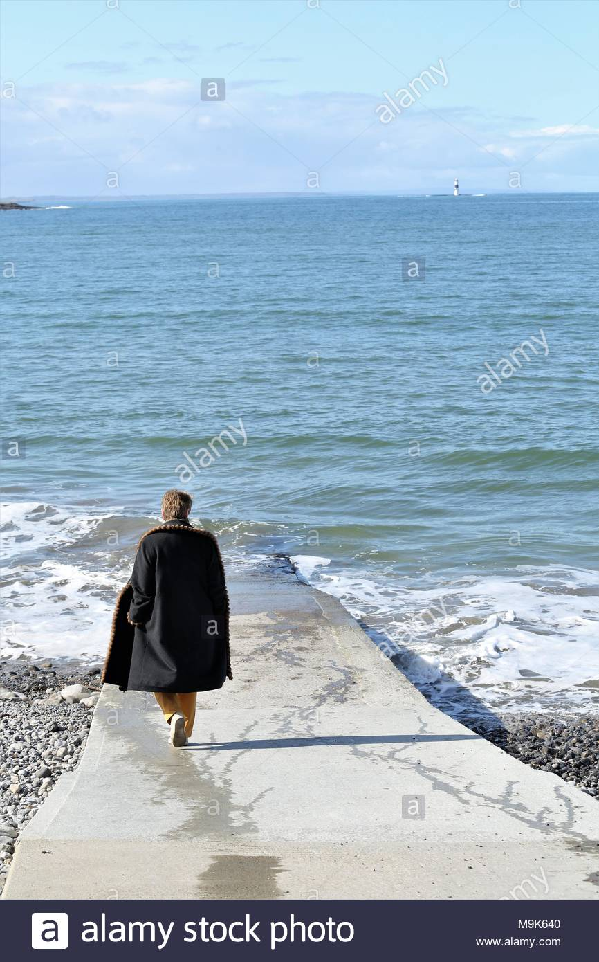 A beautiful scene as a woman walks down the slipway towards the shore at Rosses Point on the West Coast of Ireland. Credit: reallifephotos / Alamy - Stock Image