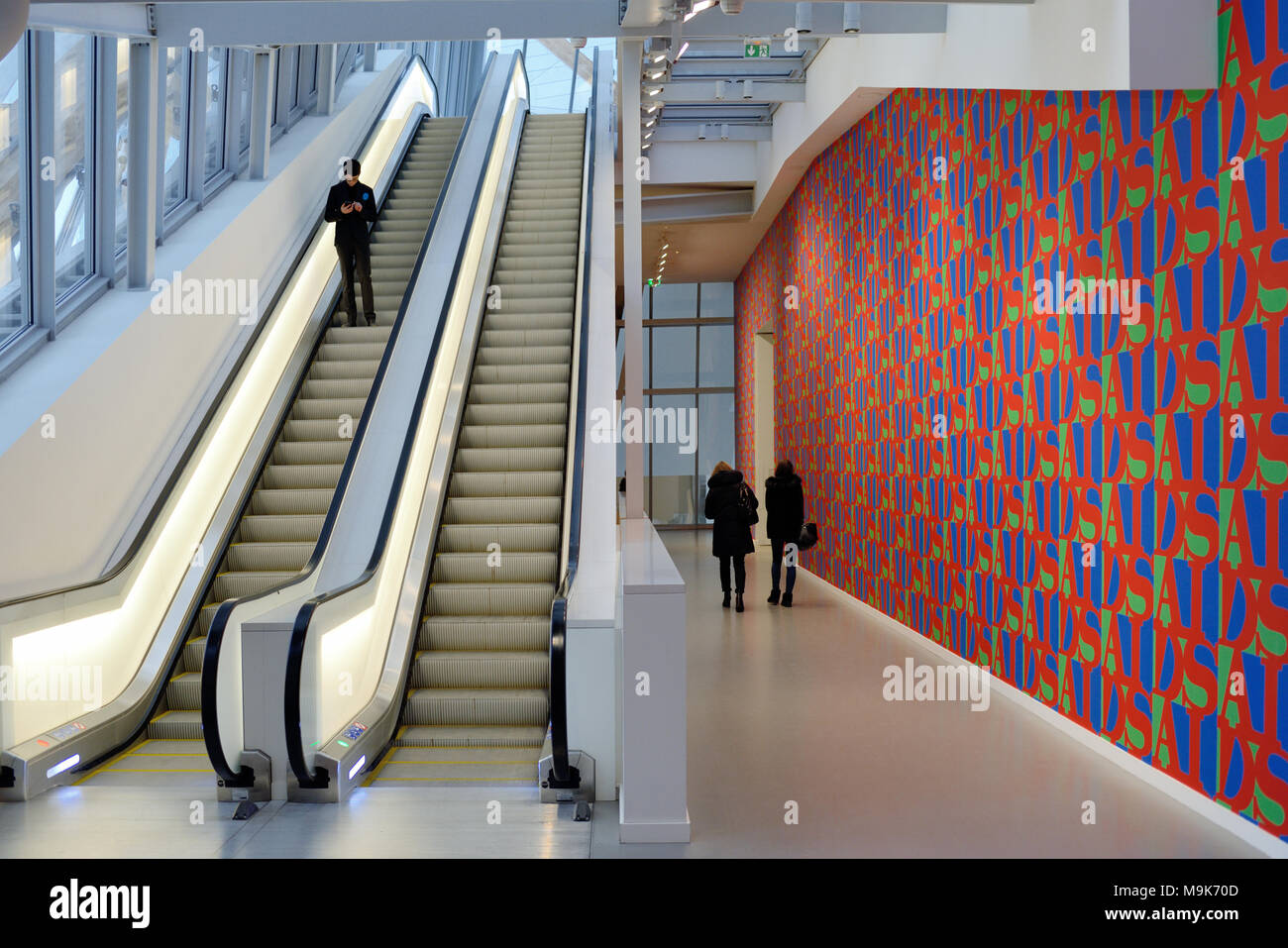Visitors, Escalators & Aids Wallpaper in Hallway at the Louis Vuitton Foundation Art Museum & Cultural Centre (2006-14) designed by Frank Gehry, Paris - Stock Image