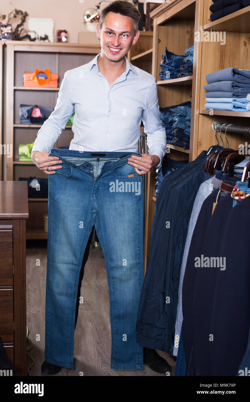 cf29c7c3 Young man is choosing on new jeans in men's clothes store Stock ...