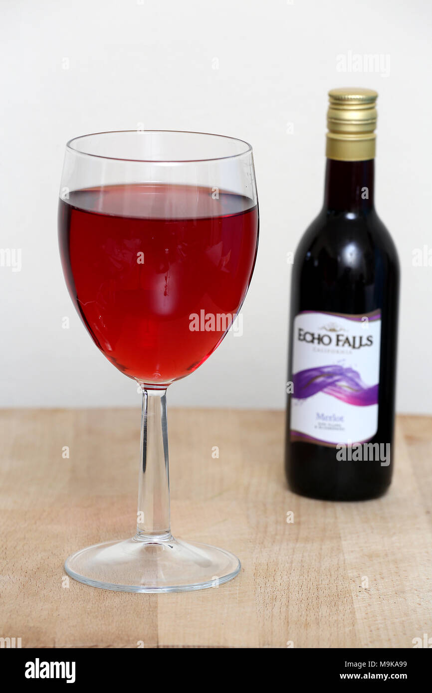 Generic image of Red Wine in a glass with bottle in the background. - Stock Image