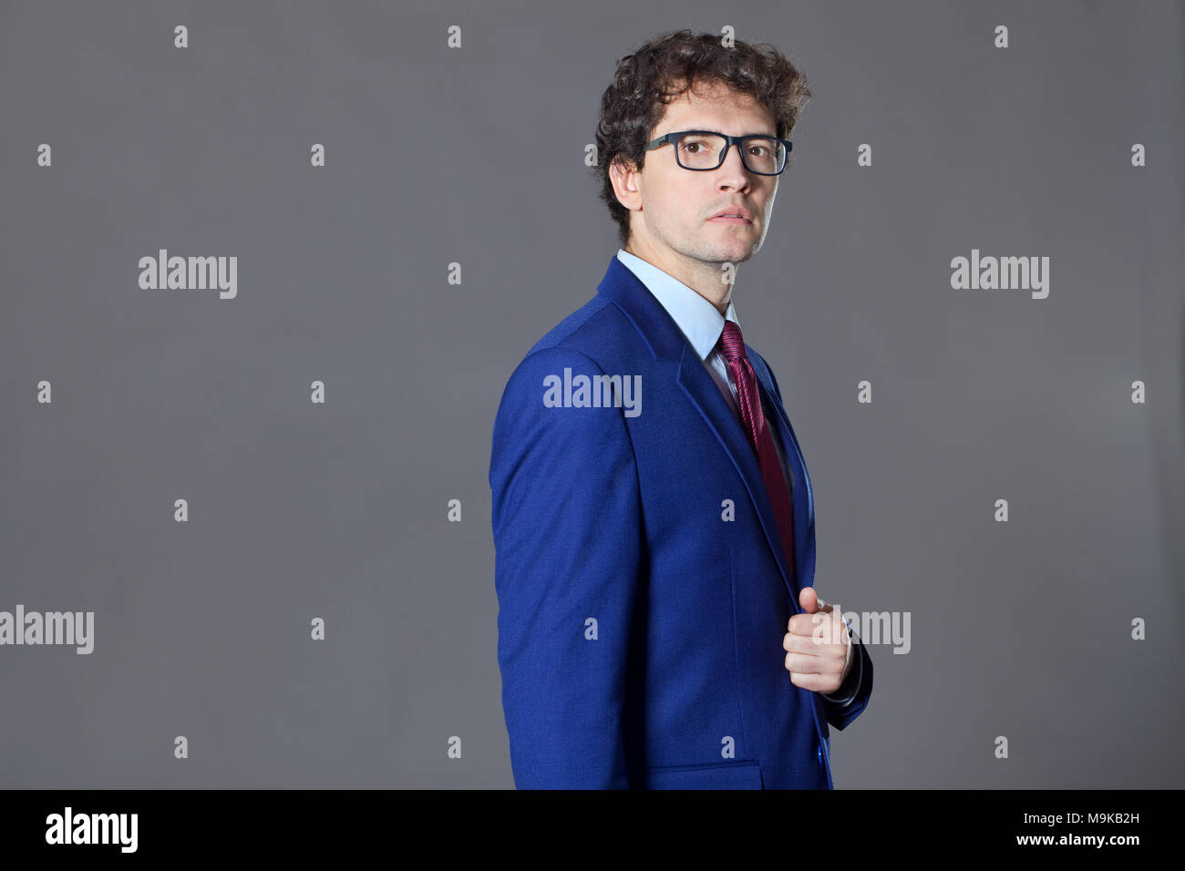 Young seriously man standing ang keeping his blue jacket Stock Photo