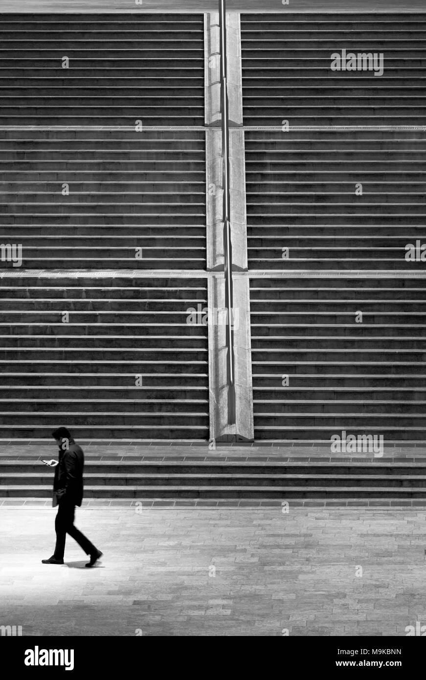 Man walking and looking at the smartphone - Stock Image