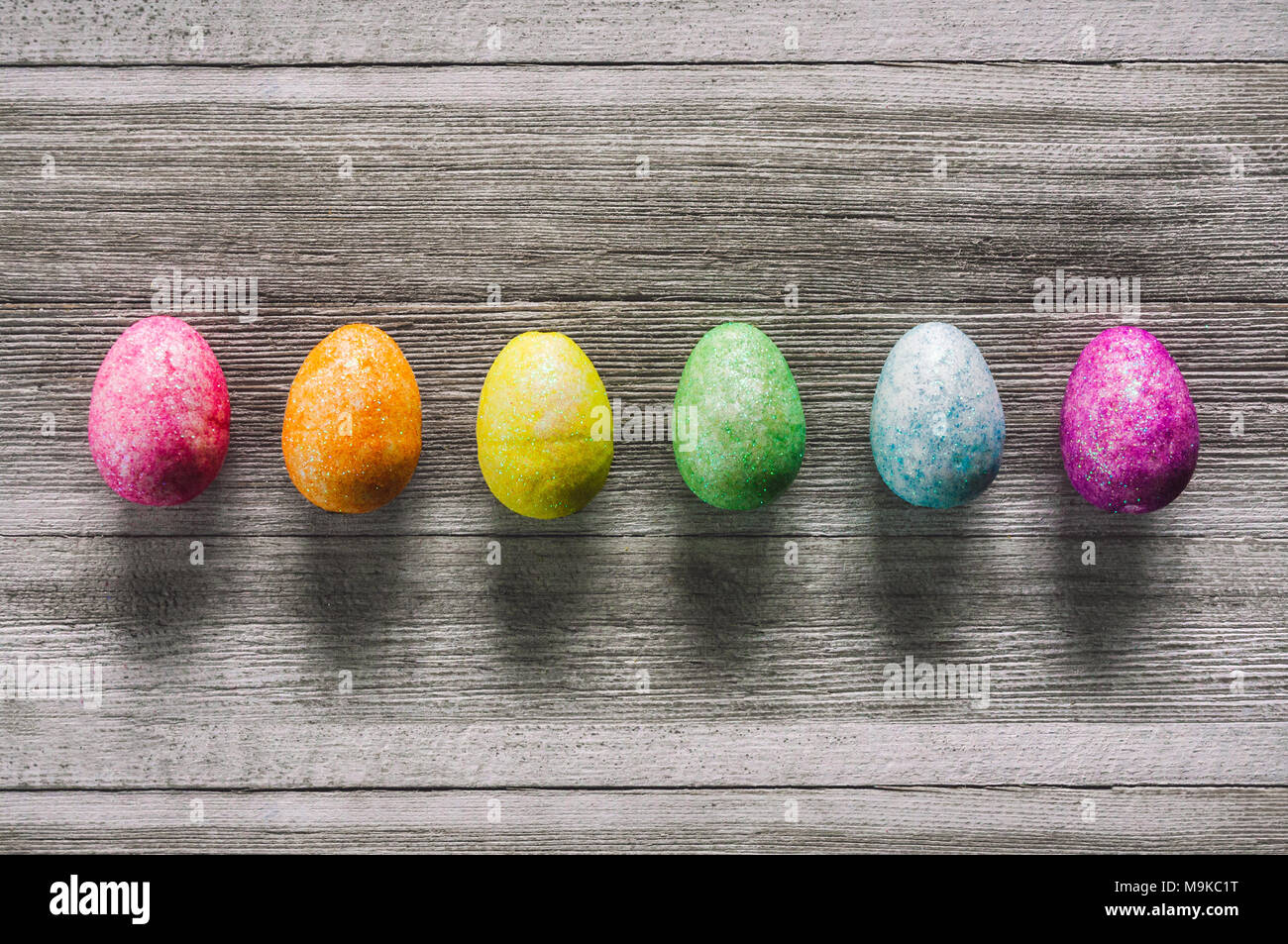 Rainbow Eggs on White Rustic Table - Stock Image