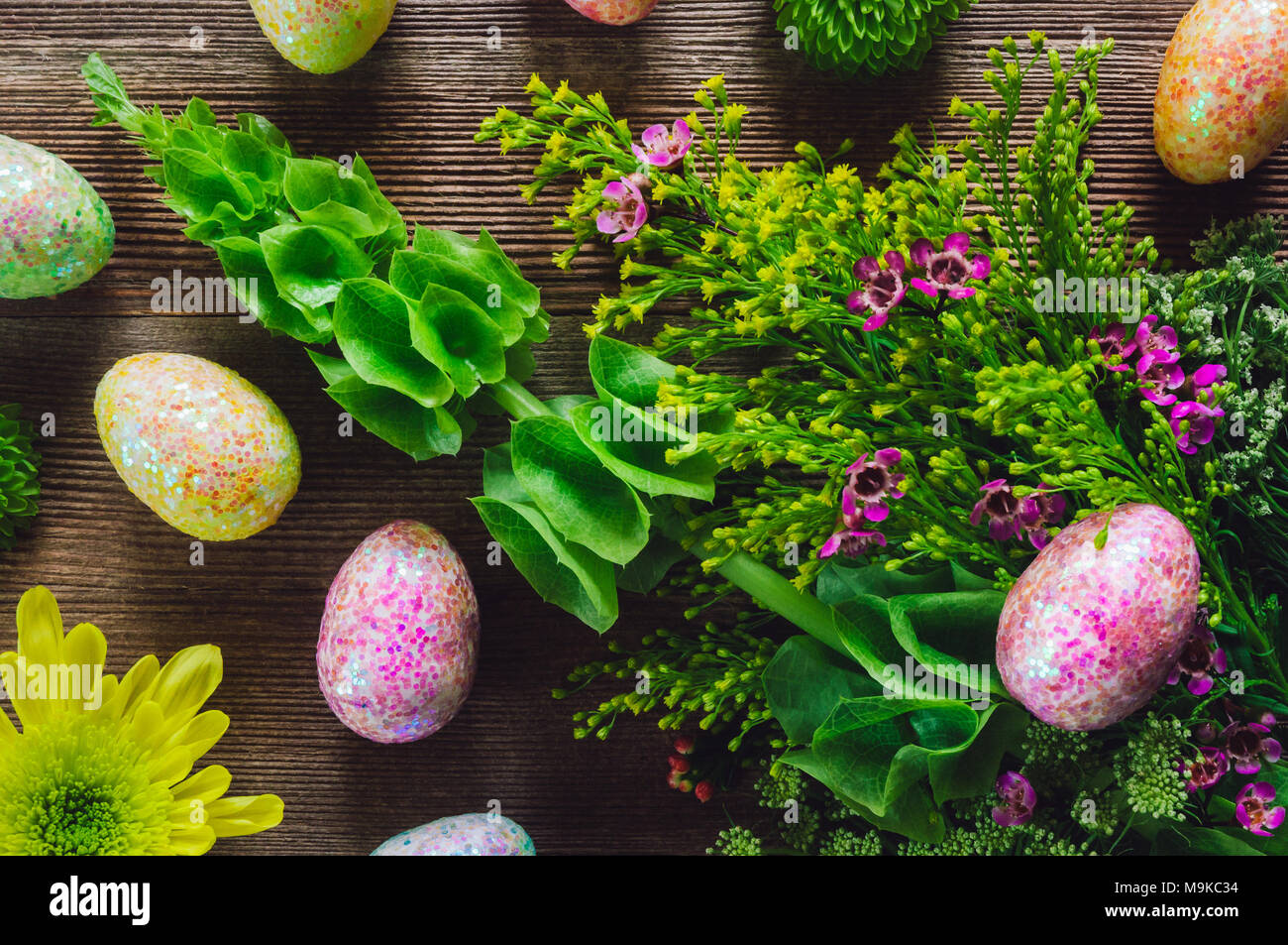 Flowering Plants with Decorated Eggs on Wood Table - Stock Image