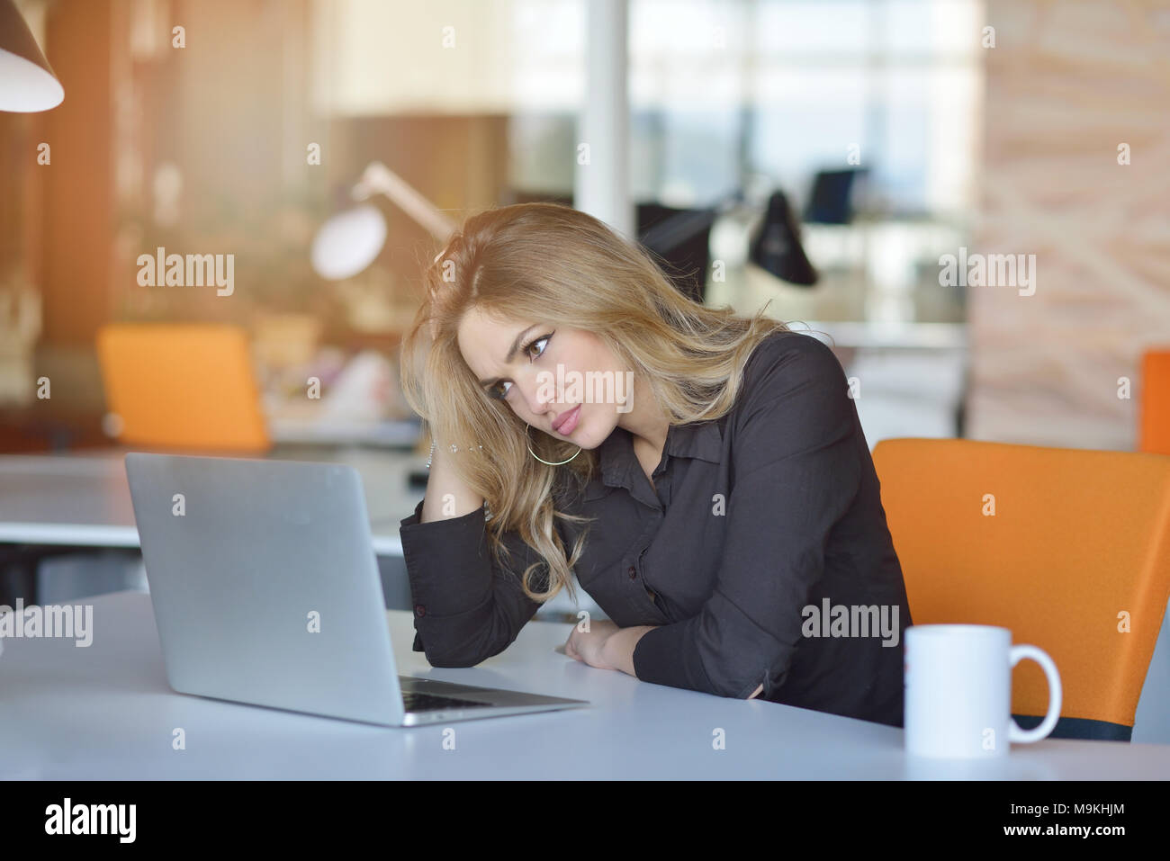 Young busy beautiful latin business woman suffering stress working at office computer - Stock Image