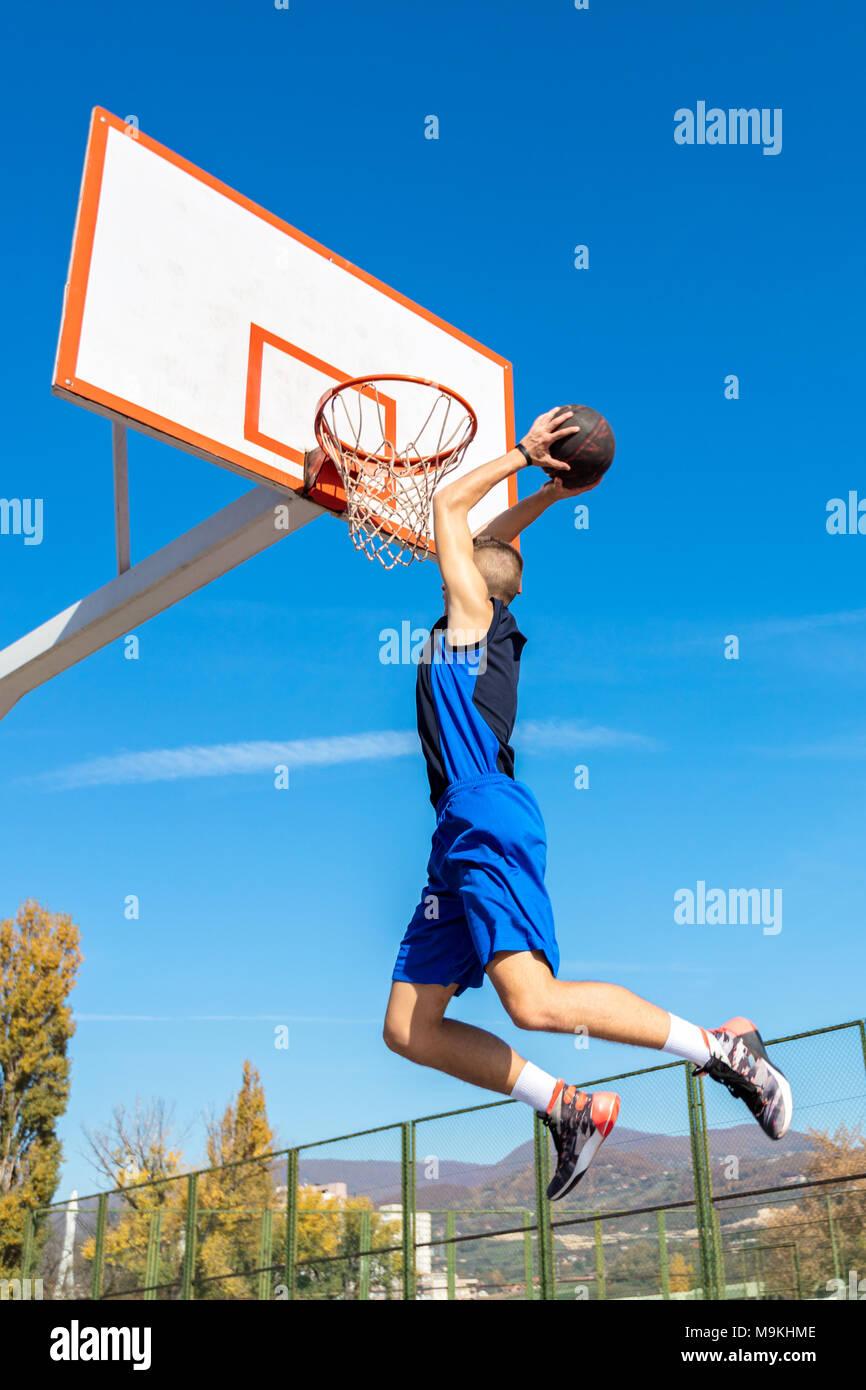 Young Basketball street player making slam dunk - Stock Image