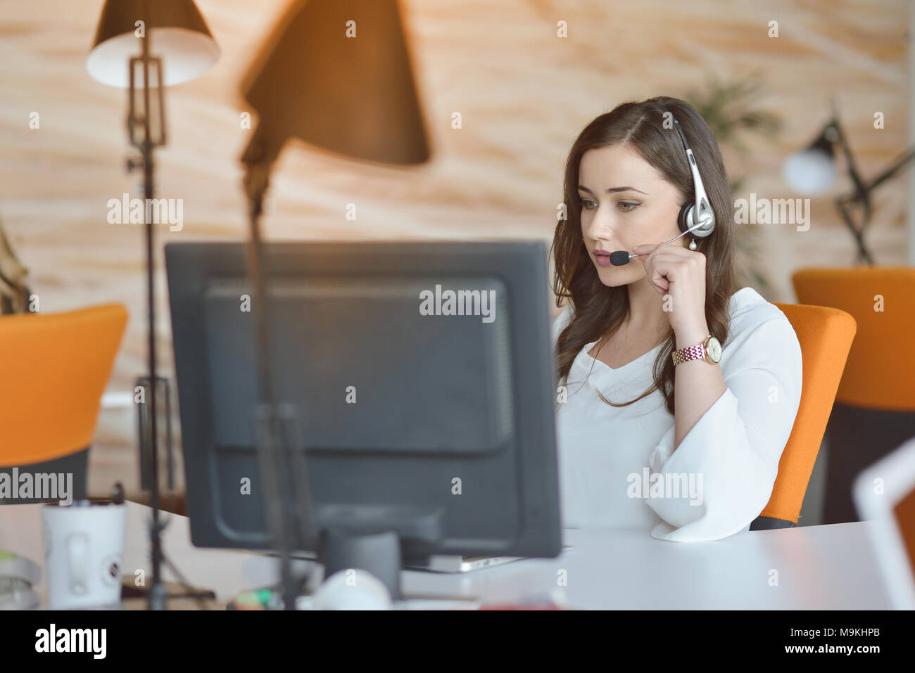 Attractive woman listening to music while working in startup business office - Stock Image