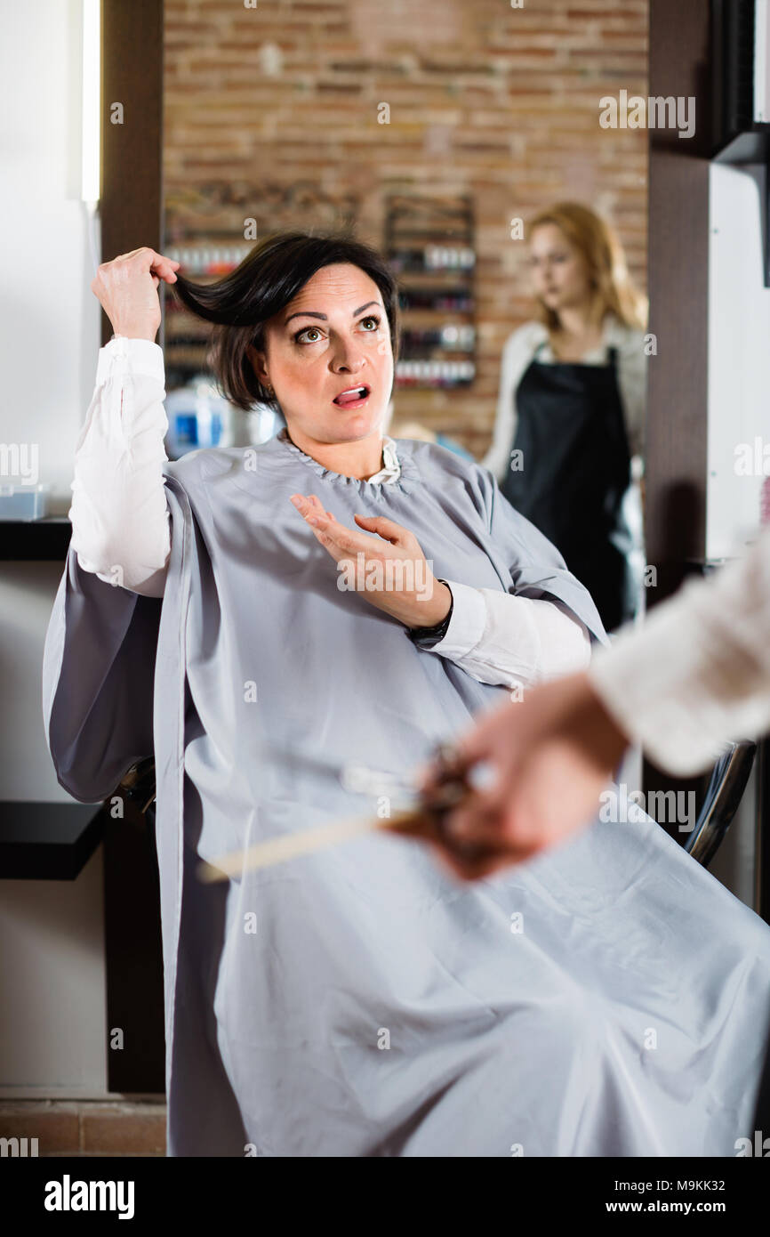 Angry woman telling to young hairdresser that she does not