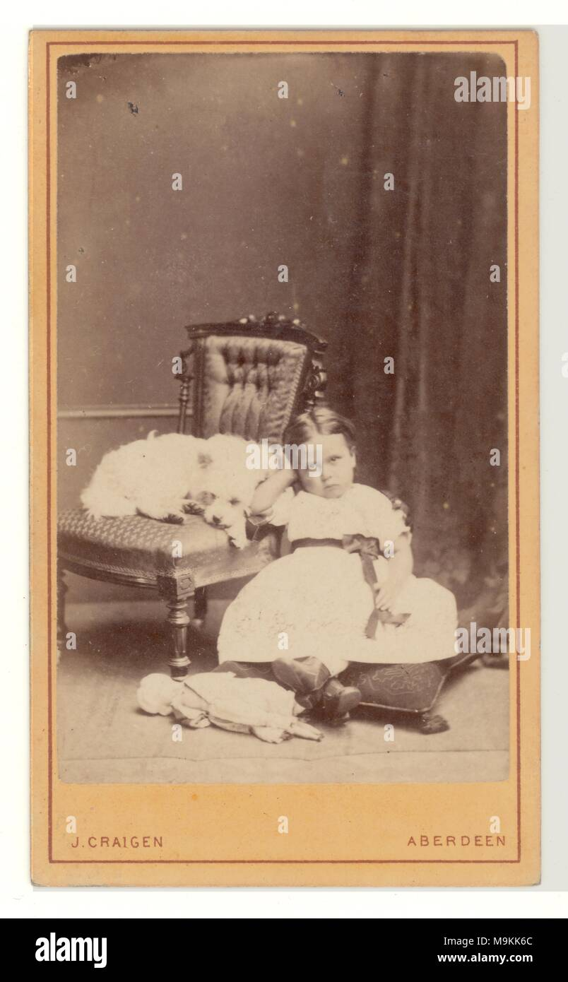 Victorian studio portrait, Carte de Visite (visiting card) of young Scottish girl sitting down wearing her best party frock, looking petulant, whilst her Cairn or West Highland terrier sits on the chair, 1860's, Aberdeen, Scotland, U.K. - Stock Image